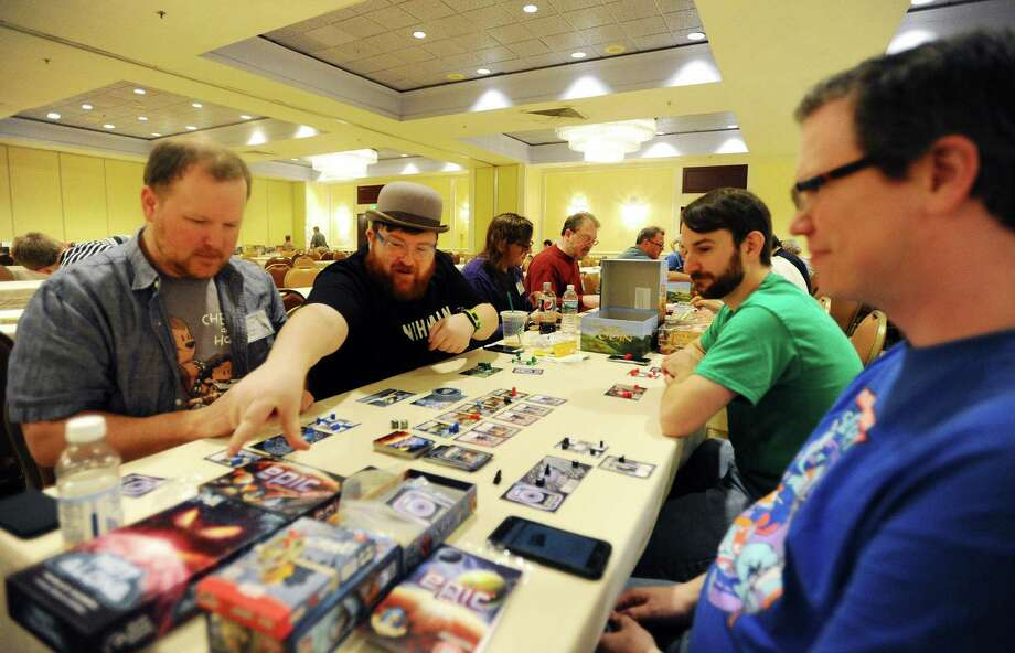 Alex Erde, center left, reaches for a card while playing the board game Tiny Epic Galaxies during the third day of ConnCon Falcon 2016, a fantasy board, card and role playing game conference inside the Stamford Marriott hotel in Stamford, Conn. on Sunday, Oct. 30, 2016. Also pictured are, counterclockwise from center left, Keith Corbino, Eric Summerer and Erik Lindberg. Photo: Michael Cummo / Hearst Connecticut Media / Stamford Advocate
