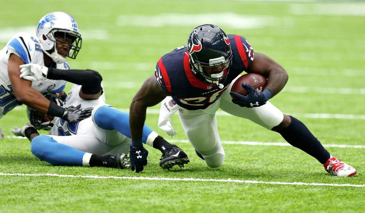 Houston Texans running back Lamar Miller (26) crawls along the turn after he was hit by Detroit Lions cornerback Adairius Barnes (38) during the second quarter of an NFL football game at NRG Stadium on Sunday, Oct. 30, 2016, in Houston.