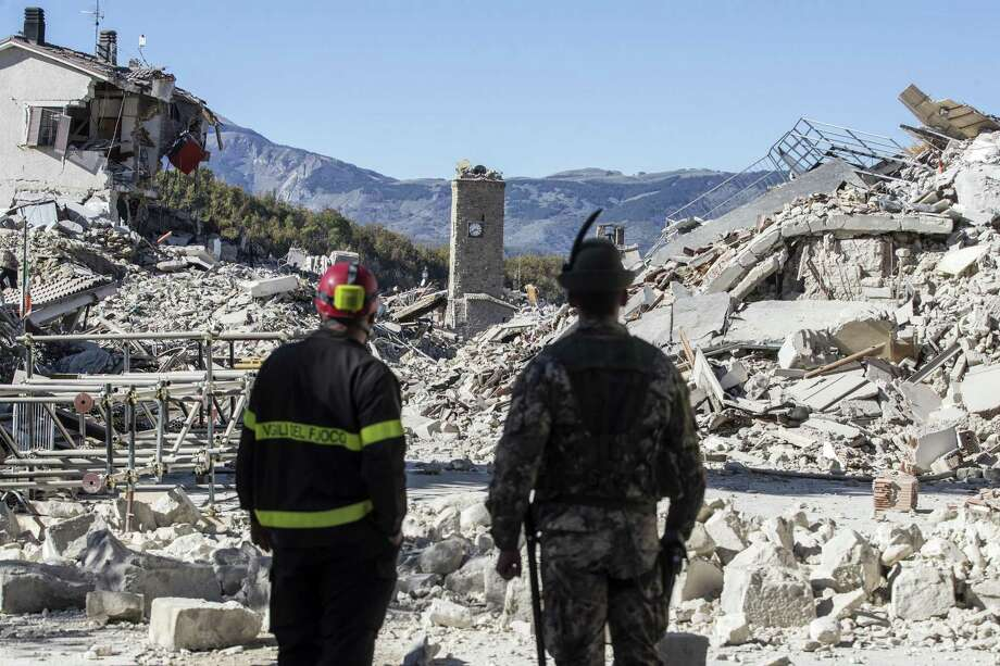 A firefighter, left, and an alpine soldier look at rubble in the town of Amatrice after an earthquake with a preliminary magnitude of 6.6 struck central Italy, Sunday, Oct. 30, 2016. A powerful earthquake rocked the same area of central and southern Italy hit by quake in August and a pair of aftershocks last week, sending already quake-damaged buildings crumbling after a week of temblors that have left thousands homeless.  (Massimo Percossi/ANSA via AP) Photo: Massimo Percossi, SUB / ANSA