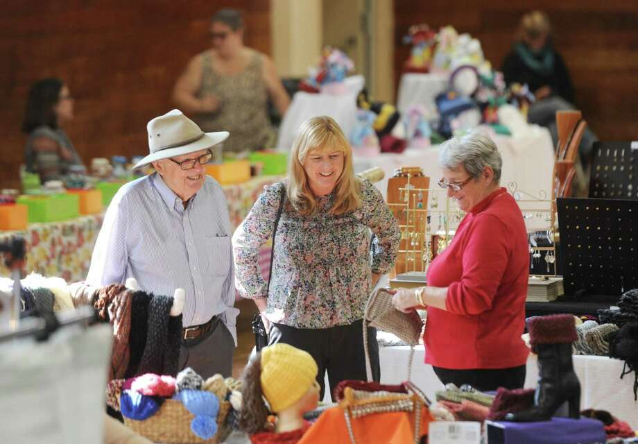 Phil Wallace, of Larchmont, N.Y., and his daughter Carol Wallace, center, of Glenville, browse Marianne Thiel's Knit Kraze stand at the New England Craft Show at the Eastern Greenwich Civic Center in Old Greenwich, Conn. Sunday, Oct. 30, 2016. Dozens of crafters from Connecticut and New England showcased and sold their work, with a variety of items including clothing, jewelry, art, food and more. Photo: Tyler Sizemore / Hearst Connecticut Media / Greenwich Time
