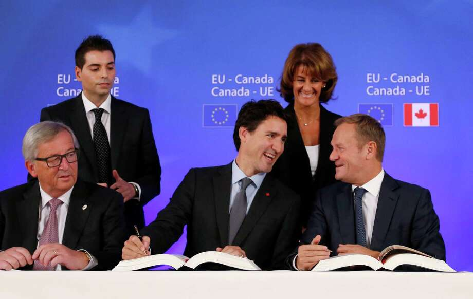 Canadian Prime Minister Justin Trudeau, center front, sits with European Commission President Jean-Claude Juncker, left, and European Council President Donald Tusk, right, as they sign the Comprehensive Economic and Trade Agreement (CETA) during an EU-Canada summit at the European Council building in Brussels, Sunday, Oct. 30, 2016.(Francois Lenoir/Pool Photo via AP) Photo: Francois Lenoir, POOL / Reuters Pool