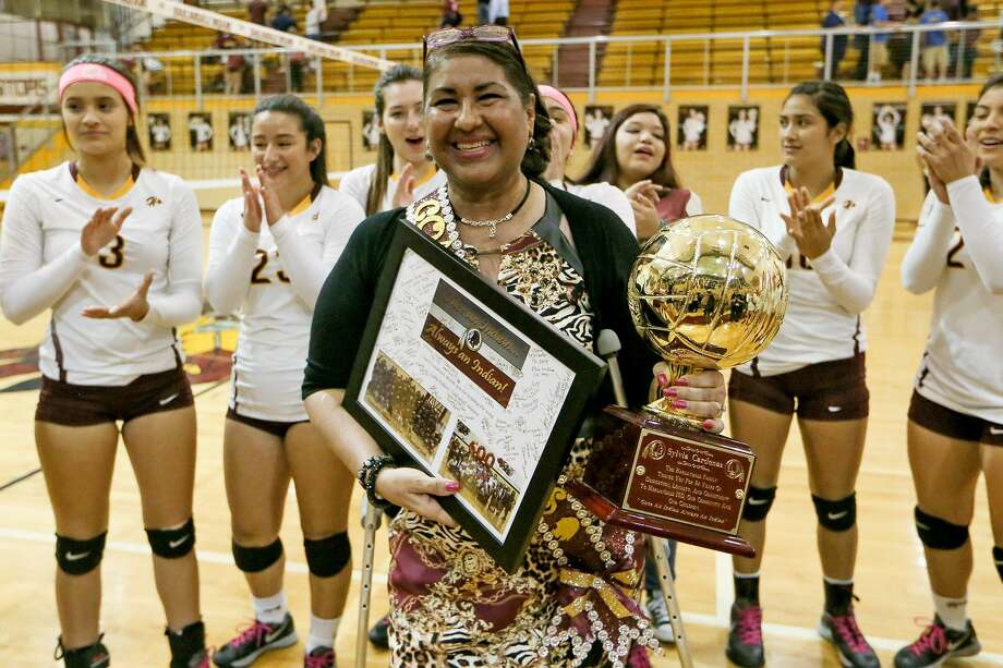 Harlandale coach Sylvia Cardenas with a trophy and a plaque awarded to her during a ceremony following their District 29-5A volleyball match with Floresville at Harlandale on Tuesday, Oct. 25, 2016.  The match was the final regular season contest for Cardenas, who is retiring after coaching the Lady Indians for the past 34 years.  MARVIN PFEIFFER/ mpfeiffer@express-news.net Photo: Marvin Pfeiffer, Staff / San Antonio Express-News / Express-News 2016