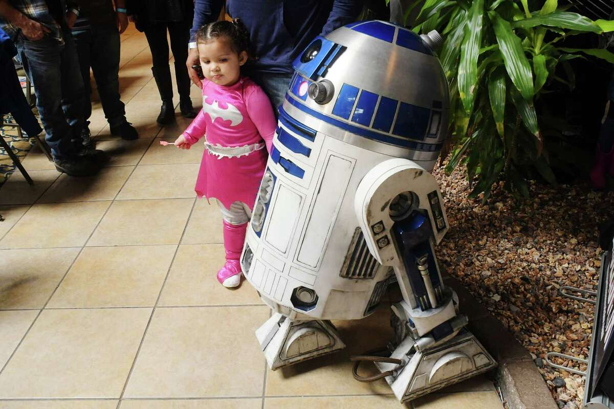 Peyton Mount, 2, dressed as Bat Girl, from Stillwater, looks over an R2D2 life-size model at the 7th annual Albany Comic Con at the Radisson Hotel on Sunday, Oct. 30, 2016, in Albany, N.Y. (Paul Buckowski / Times Union)