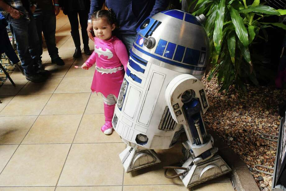 Peyton Mount, 2, dressed as Bat Girl, from Stillwater, looks over an R2D2 life-size model at the 7th annual Albany Comic Con at the Radisson Hotel on Sunday, Oct. 30, 2016, in Albany, N.Y.   (Paul Buckowski / Times Union) Photo: PAUL BUCKOWSKI / 20038603A