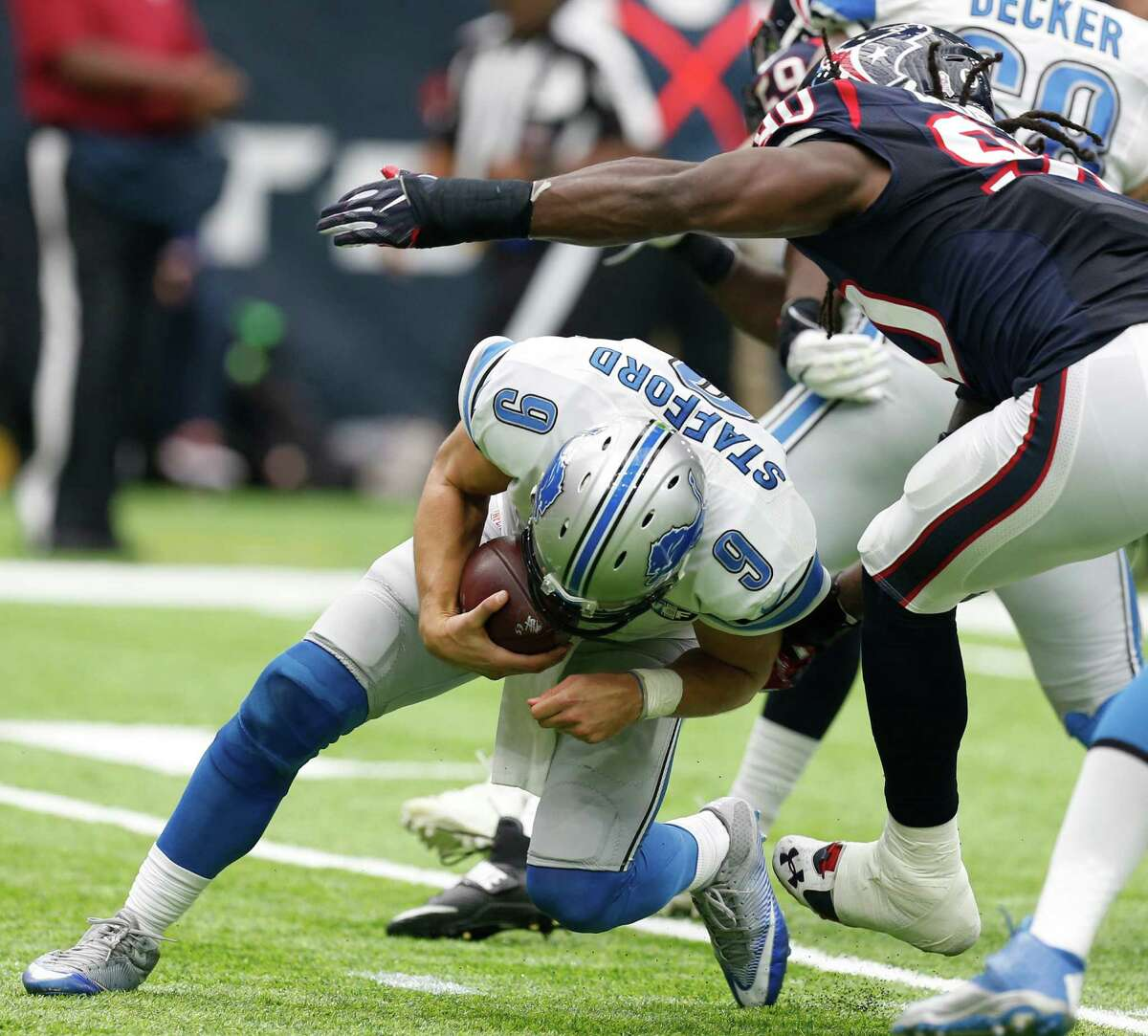 The Lions' Matthew Stafford (9) is sacked by Texans defensive end Jadeveon Clowney (90) during the second quarter. It was the only sack of the game for the Texans.