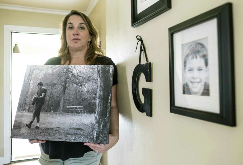 """Sherene Mayner, the mother of Garrett McKinney, holds one of her favorite photos of him. She said McKinney was diagnosed with paranoid schizophrenia in 2014. """"He really wished he was not sick,"""" she said. """"He cried a lot about that."""" Photo: RODOLFO GONZALEZ, STAFF PHOTOJOURNALIST / AUSTIN AMERICAN-STATESMAN"""