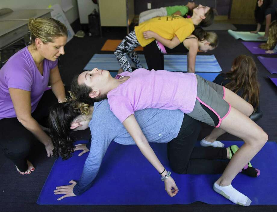 Middle school teacher Rachel Mann assists eighth-graders Leah Brill, top, and Rachel Meiliken with a yoga pose during a yoga class at Carmel Academy in Greenwich on Wednesday. Mann recently got yoga certification and began teaching the middle school elective course for students as well as a longer, more intensive class for teachers at Carmel. Photo: Tyler Sizemore / Hearst Connecticut Media / Greenwich Time