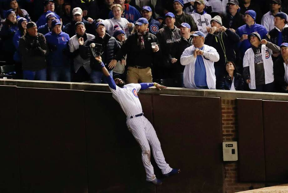 With fans at Wrigley Field making it a point to stay out of the way, Cubs right fielder Jason Heyward catches a fly ball hit by the Indians' Trevor Bauer in the third inning Sunday night. Photo: Charles Rex Arbogast, STF / Copyright 2016 The Associated Press. All rights reserved.