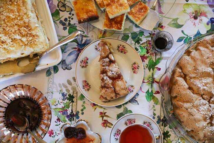 Traditional Russian desserts including a napoleon cake (left), cottage cheese cake (top) and apple pie (center,right) are seen on the dining room table of Frina Nemchenok, in her home in San Francisco, California, on Tuesday, Oct. 18, 2016.