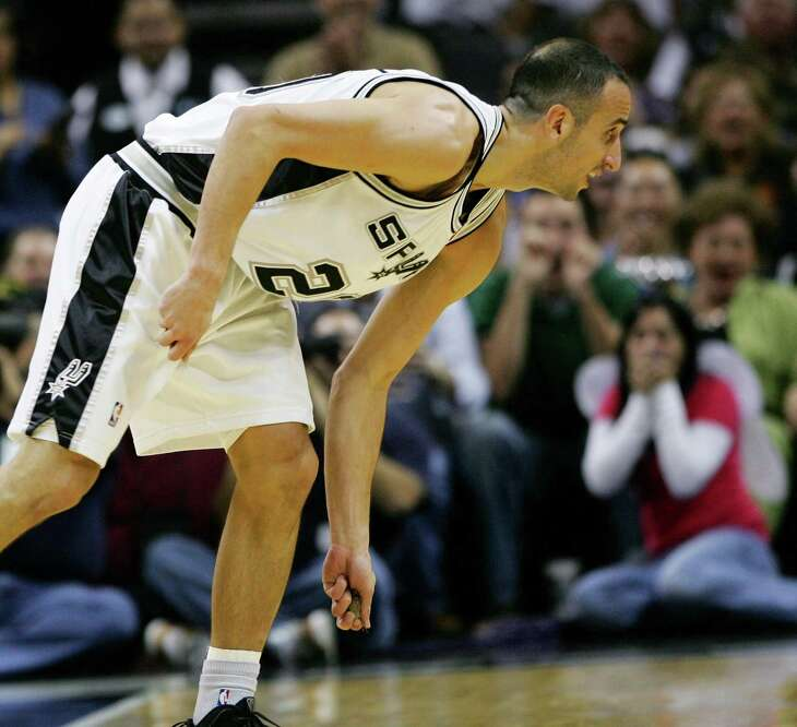 San Antonio Spurs guard Manu Ginobili picks up a bat to remove it from the court after swatting the animal from the air as it flew around the AT&T Center on Oct. 31, 2009.