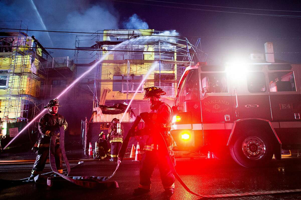 Leonard Jung, an engineer with the Oakland Fire Department, adjusts hose while battling a fire at 329 Lester Ave. in Oakland, Calif., on Monday, Oct. 31, 2016. The fire erupted before dawn at a condo complex under construction near Lake Merritt.