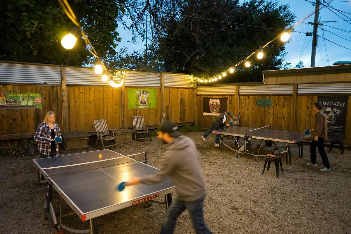 Randi Pfaff, left, plays a game of ping pong with Bryan Rood at Beer Thirty in Soquel, Calif. on Saturday, Oct. 29, 2016. Beer Thirty offers a wide variety of beers and is dog friendly.