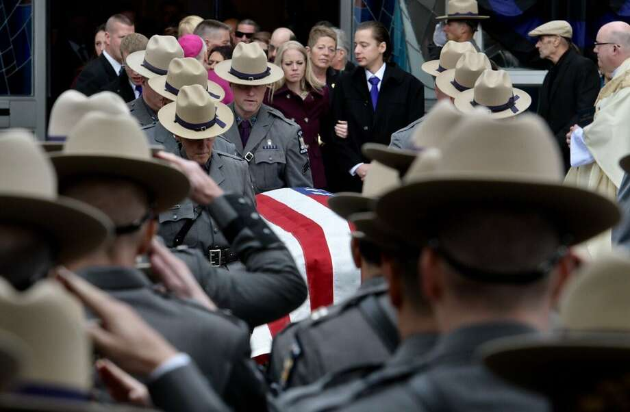 State Police salute Trooper Timothy Pratt's casket as its brought out of St. Michael's Church in South Glens Falls. Pratt's family followed behind the casket. (Skip Dickstein / Times Union)