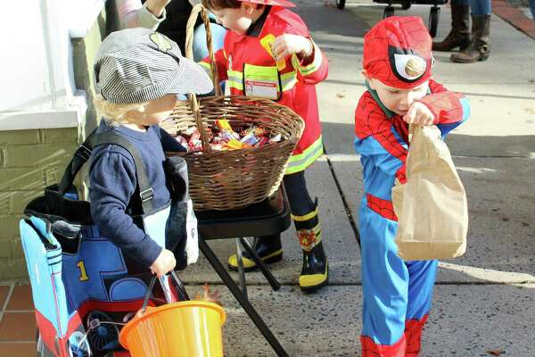 Riley Cahill (left), 2, looks on as Hunter Grambling, 2, checks out his candy from the Mom's Morning In Halloween Parade on Oct. 28, 2016 in Darien, CT.