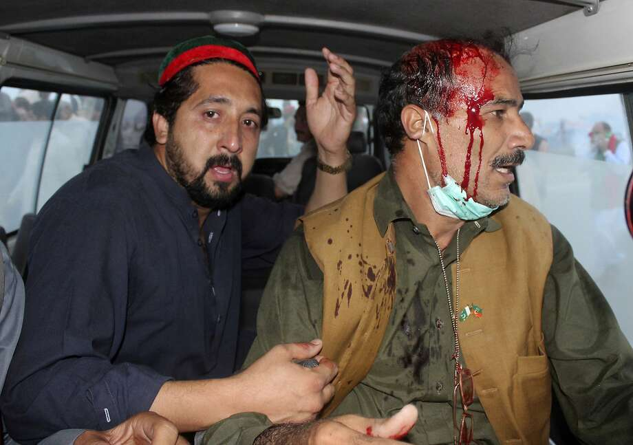 A supporter of Imran Khan's Pakistan Tehreek-e-Insaf party, helps a fellow protester during a clash with government forces in Hazro, Pakistan, Monday, Oct. 31, 2016. Pakistani police launched a nation-wide crackdown overnight, arresting at least 1,500 supporters of Khan ahead of an opposition rally planned later this week in Islamabad, officials said Monday. (AP Photo/Mohammad Sajjad) Photo: Mohammad Sajjad, Associated Press