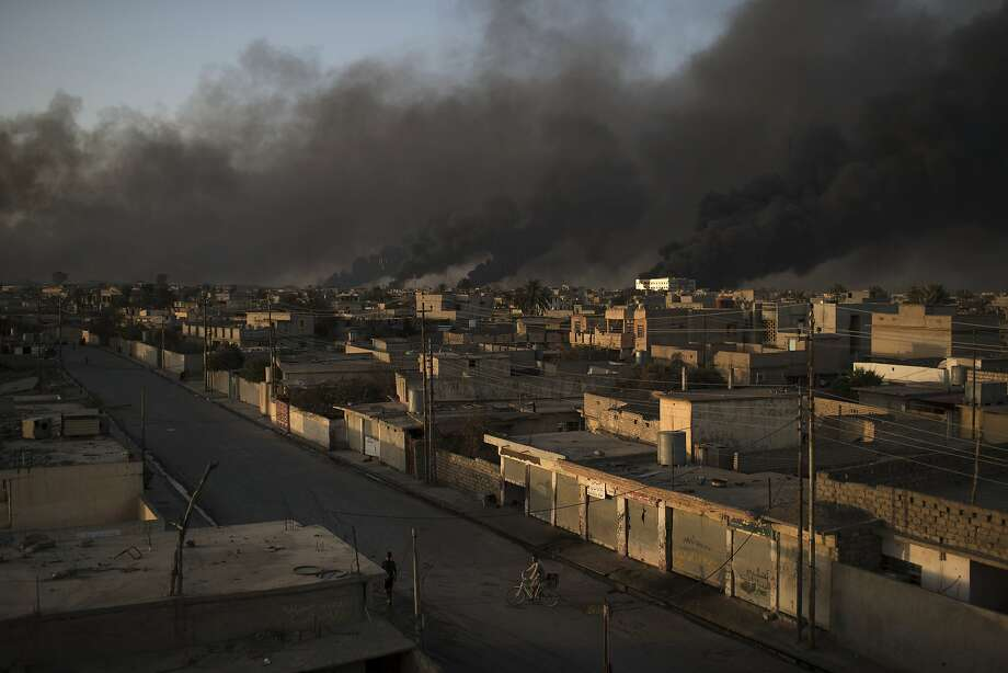 A cyclist rides in Qayara, Iraq, about 30 miles south of Mosul, as smoke rises from burning oil fields. Islamic State extremists captured Mosul in 2014 as they swept into Iraq and Syria. Photo: Felipe Dana, Associated Press