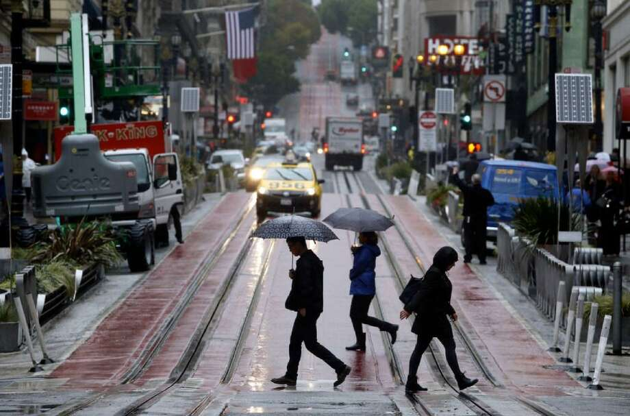 Pedestrians carry umbrellas as they traverse Powell street at Ellis on Friday, Oct. 14, 2016, in San Francisco. Rain was expected to return Monday evening for Halloween. Photo: Paul Chinn / The Chronicle / /