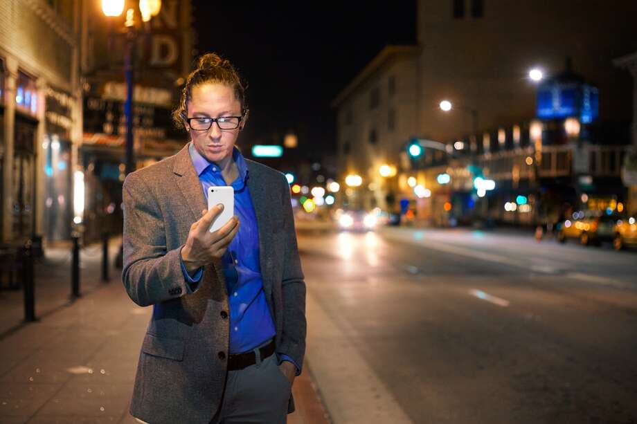 A man ride share car with his phone on an Oakland city street.