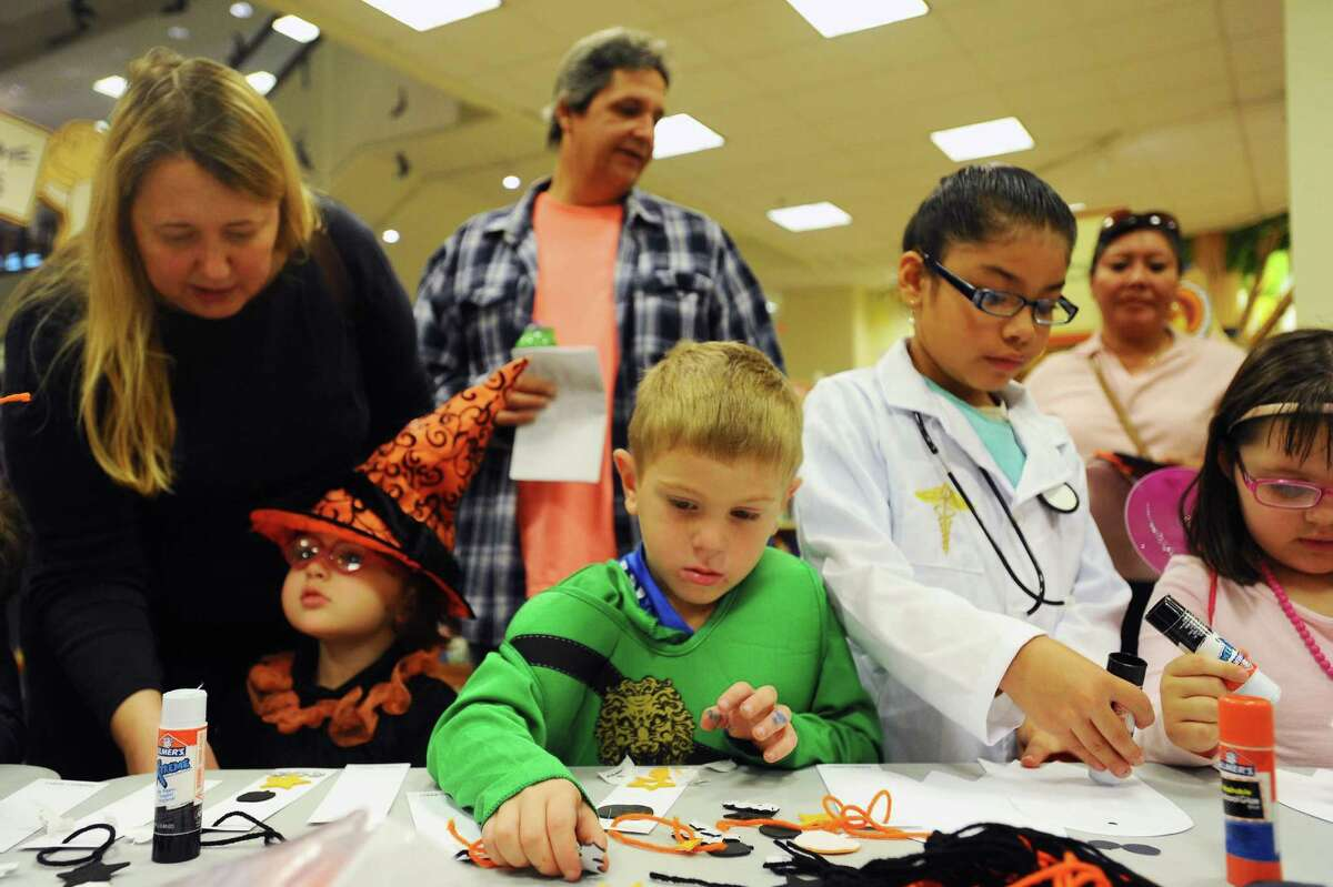 Ninja Mat Lupinacci, 4, reaches for a sticker while making a book mark during the Stamford Public Education Foundation's Halloween Book Fair at Barnes & Noble in Stamford, Conn. on Sunday, Oct. 30, 2016.
