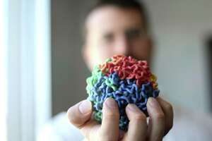 Erez Aiden, 35, who is in charge of the center for genomics at Baylor College of Medicine holds a model on Wednesday, Dec. 23, 2015, in Houston. ( Elizabeth Conley / Houston Chronicle )