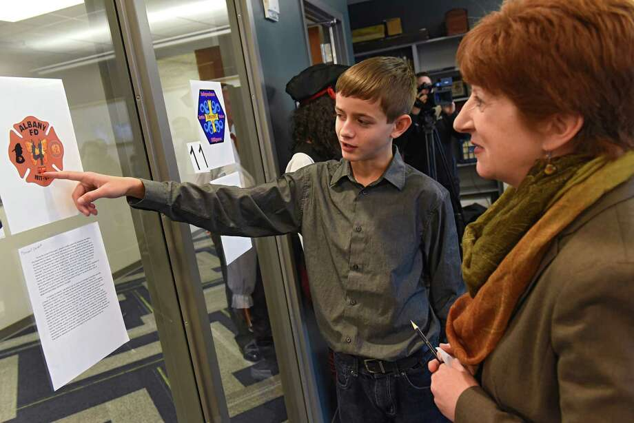Mayor Kathy Sheehan checks out Maxwell Lockett's patch design as she helps members of the Albany Fire Department select three design finalists for their new Engine 4 patch at Tech Valley High School located at SUNY Poly campus on Monday, Oct. 31, 2016 in Albany N.Y. The winning design will form the basis for a new patch that will be worn on uniforms of the firefighters from Engine 4, which covers Washington Avenue Extension area. Maxwell was the third place finalist. (Lori Van Buren / Times Union) Photo: Lori Van Buren / 20038605A