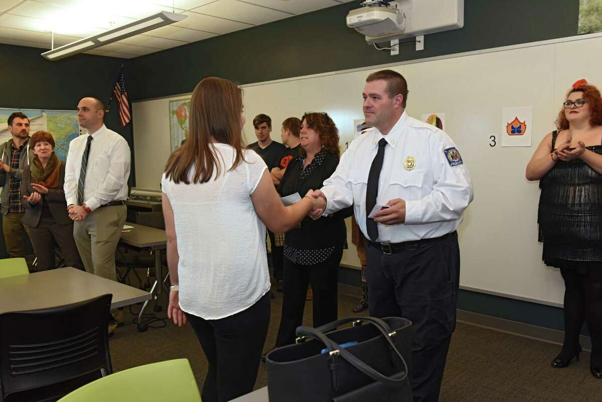 Isobella Grubb-Kavach receives the first place award from Battalion Chief Geo Henderson after members of the Albany Fire Department and Mayor Kathy Sheehan selected three design finalists for their new Engine 4 patch at Tech Valley High School located at SUNY Poly campus on Monday, Oct. 31, 2016 in Albany N.Y. Her winning design will form the basis for a new patch that will be worn on uniforms of the firefighters from Engine 4, which covers Washington Avenue Extension area. Maxwell was the third place finalist. (Lori Van Buren / Times Union)