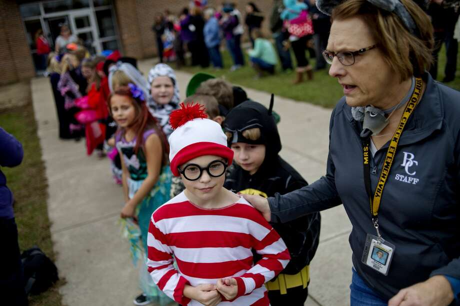 Dress as Waldo from the 'Where's Waldo?' books, second grader Landon Williams, left, follows teacher Dawn Chartier's lead in starting the Halloween costume parade on Monday at Bullock Creek Elementary School. Students from each class line up and walk around the path behind the school. The parade takes place at the end of the day after each class has had their celebrations. Photo: NICK KING ,  Nking@mdn.net