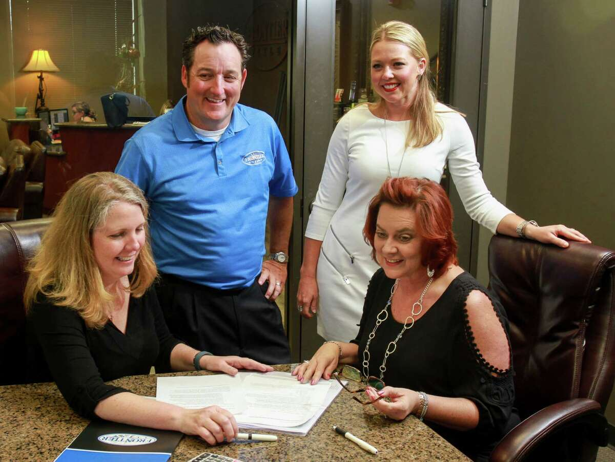 Becky Steinbrecher, from left, Frontier Title president Doug Watson, Keri Burdette and Paula Rodgers review files at Frontier Title. (For the Chronicle/Gary Fountain, October 4, 2016)
