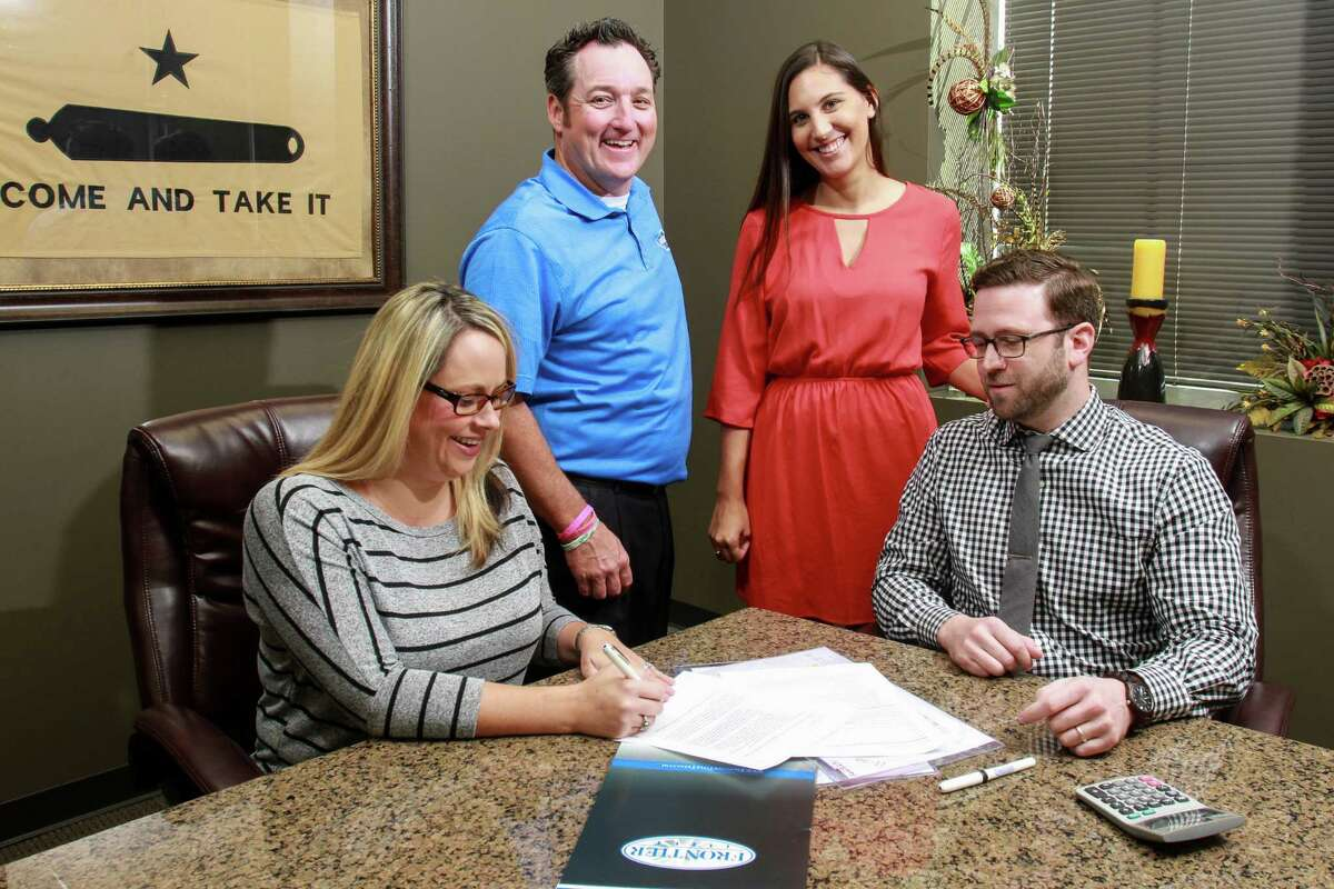 Frontier Title's Sarah Wheat, left, and Tyler Ramsey, right, review files. With them are owner Doug Watson and Shea Angelle.