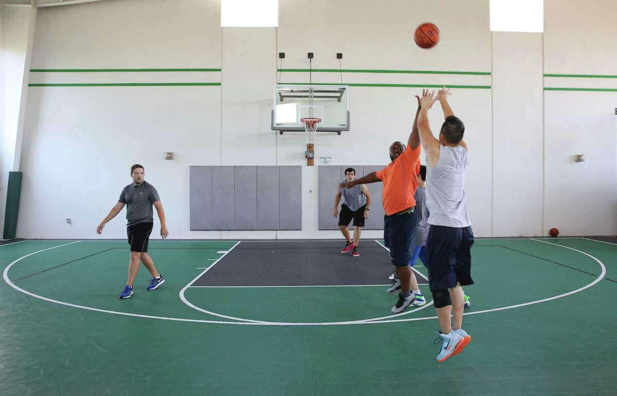 Heavy Construction Systems Specialist employees play basketball games during lunch hour Wednesday, Sept. 28, 2016, in Sugar Land. HCSS provides benefit activities, including an outdoor track and basketball courts and fitness programs, for the employees. (Yi-Chin Lee / Houston Chronicle )