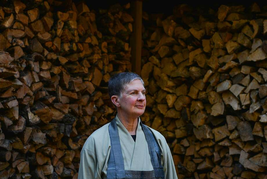 Linda Ruth Cutts, an abbess at the Tassajara Zen Mountain Center, stands in front of firewood chopped by the Alpine Hotshots firefighting crew in October. Photo: Brandon Chew, Special To The Chronicle