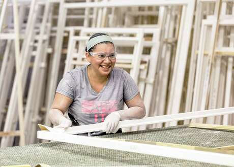 Yamileth Martinez sands frames at Rockwood Shutters, Blinds and Draperies, the No. 1 midsize company on the Top Workplaces list.