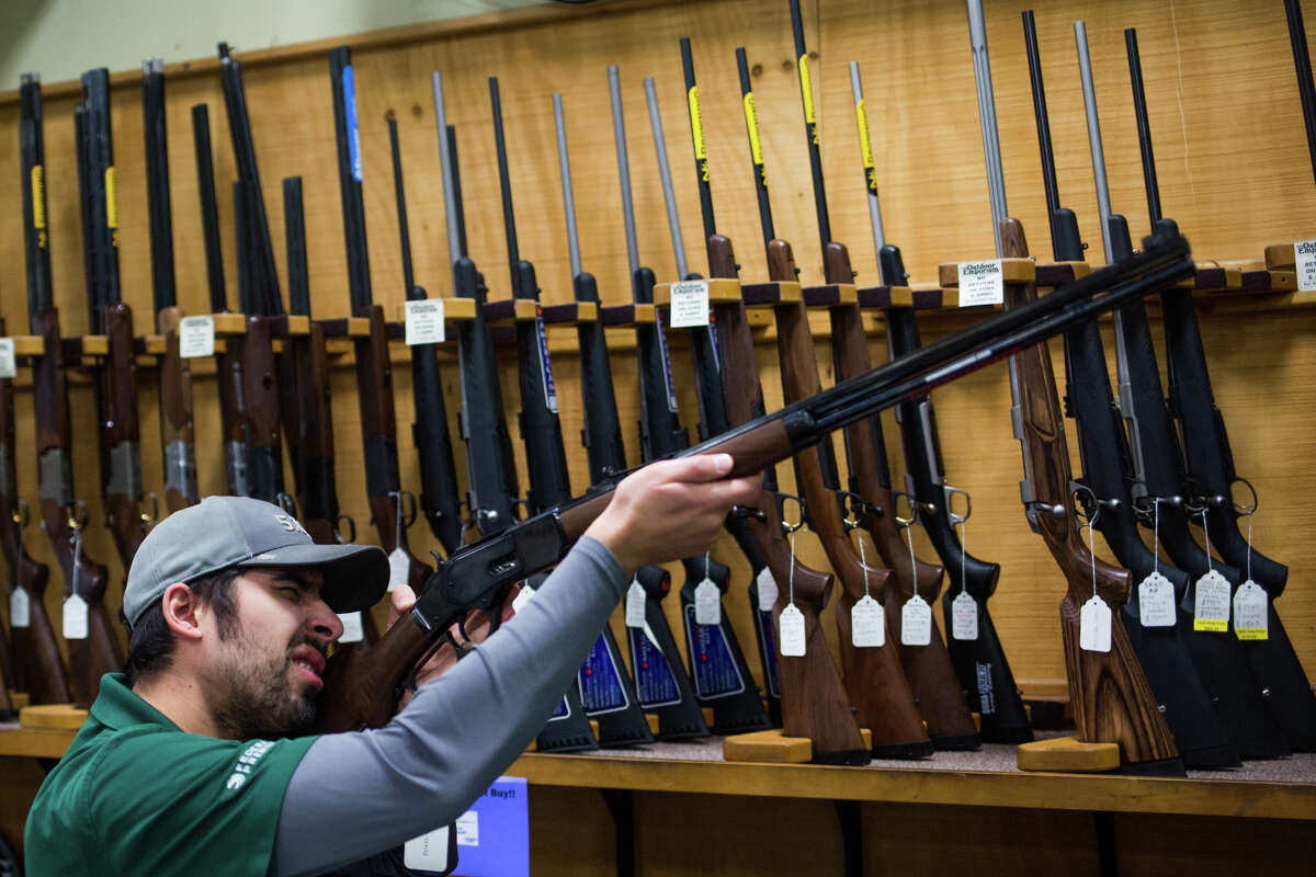 Steven Aragon looks down the sights of some new stock in the gun room at Outdoor Emporium on Tuesday, Oct. 25, 2016. Shop owners say Seattle's new gun and ammunition tax enacted this year has hurt sales and the city hasn't been transparent with the funds collected.