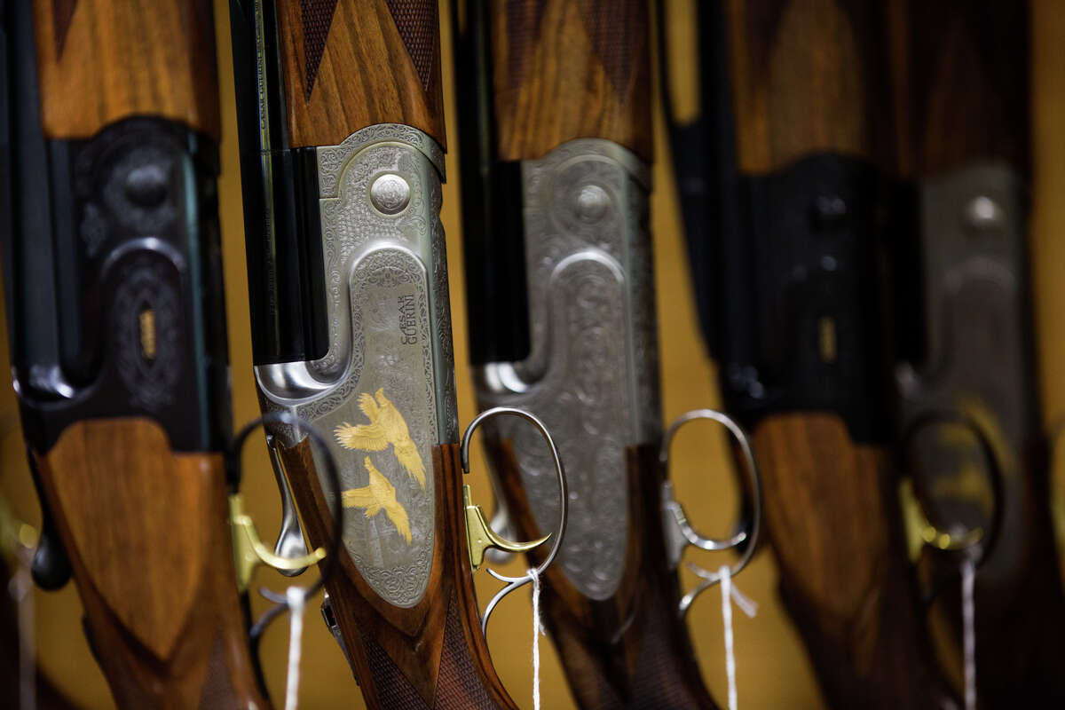 A row of embellished rifles fills a shelf in the gun room at Outdoor Emporium on Tuesday, Oct. 25, 2016.