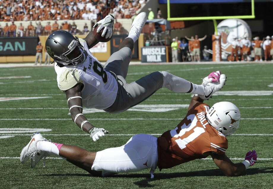 Baylor wide receiver Ishmael Zamora (8) is upended by Texas safety Jason Hall (31) as he scores a touchdown on a 20-yard pass during the first half on Oct. 29, 2016, in Austin. Photo: Eric Gay /Associated Press / Copyright 2016 The Associated Press. All rights reserved.