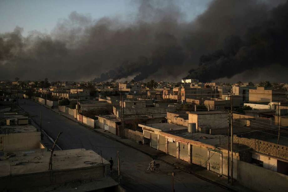 A man rides his bike on a street as smoke rises from burning oil fields in Qayara, some 50 kilometers south of Mosul, Iraq, Monday, Oct. 31, 2016. For two weeks, Iraqi forces and their Kurdish allies, Sunni tribesmen and Shiite militias have been converging on Mosul from multiple directions to drive Islamic State militants from Iraq's second largest city. (AP Photo/Felipe Dana) Photo: Felipe Dana, STF / Copyright 2016 The Associated Press. All rights reserved.
