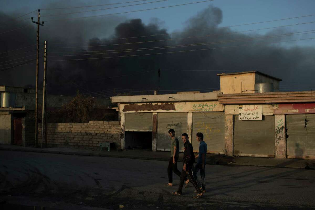 People walk on a street as smoke rises from burning oil fields in Qayara, some 50 kilometers south of Mosul, Iraq, Monday, Oct. 31, 2016. For two weeks, Iraqi forces and their Kurdish allies, Sunni tribesmen and Shiite militias have been converging on Mosul from multiple directions to drive Islamic State militants from Iraq's second largest city. (AP Photo/Felipe Dana)
