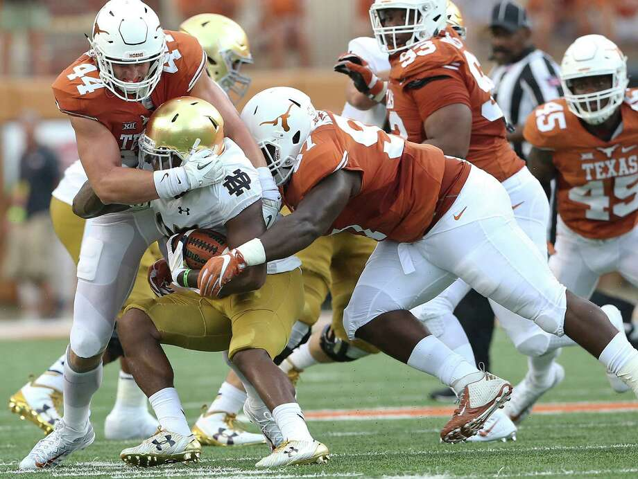 Longhorn defenders Breckyn Hager (44) and Chris Nelson get in to stop Josh Admas at the line as Texas hosts Notre Dame at DKR Stadium on September 4, 2016. Photo: TOM REEL, STAFF / 2016 SAN ANTONIO EXPRESS-NEWS