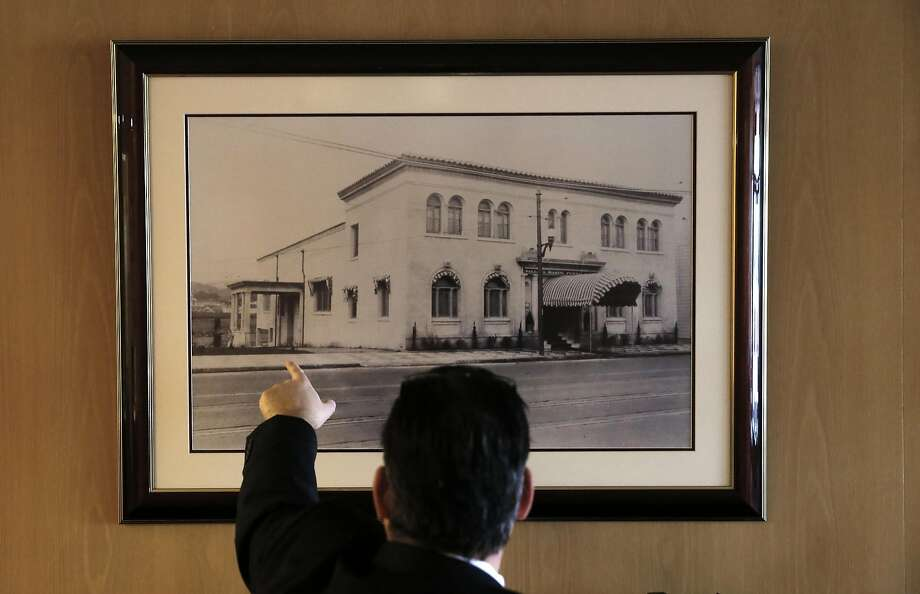 Matt Taylor displays a 1925 photograph of his family's Valente Marini Perata & Co. funeral home. Photo: Michael Macor, The Chronicle
