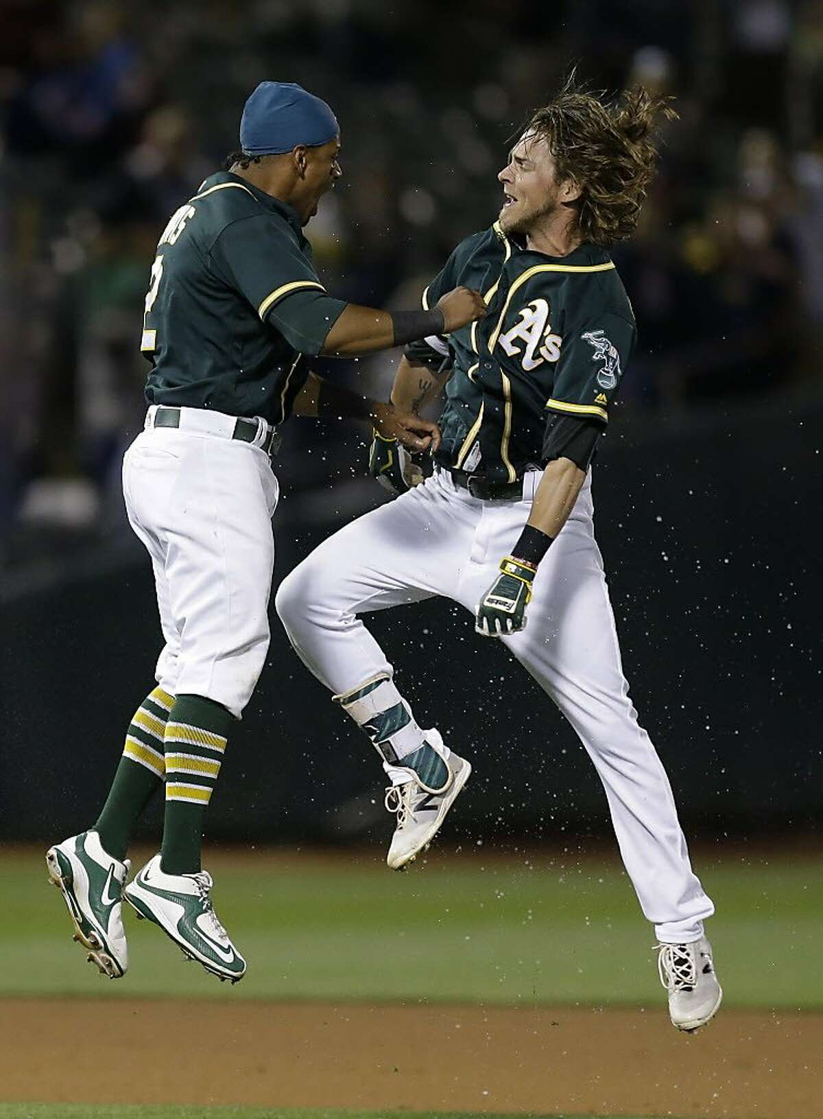 Oakland Athletics' Josh Reddick, right, celebrates with Khris Davis after making the game winning hit in the tenth inning of a baseball game against the Houston Astros Tuesday, July 19, 2016, in Oakland, Calif. (AP Photo/Ben Margot)