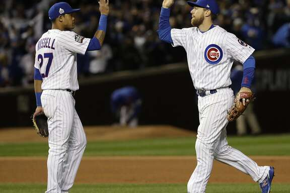 Chicago Cubs' Ben Zobrist and Addison Russell celebrate after Game 5 of the Major League Baseball World Series against the Cleveland Indians Sunday, Oct. 30, 2016, in Chicago. The Cubs won 3-2 as the Indians lead the series 3-2. (AP Photo/David J. Phillip)