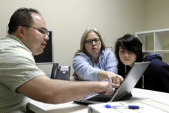 FILE - In this Feb. 12, 2015, file photo, Enrollment counselor Vue Yang, left, goes over some of the health insurance plans available to Laura San Nicolas, center, accompanied by her daughter, Geena, 17, while enrolling for health insurance at Sacramento Covered in Sacramento, Calif. Peter Lee, executive director of Covered California, announced, Tuesday, July 19, 2016, that the average monthly insurance premiums will increase by 13 percent next year for people who buy health care coverage through the state's insurance exchange. (AP Photo/Rich Pedroncelli,file)
