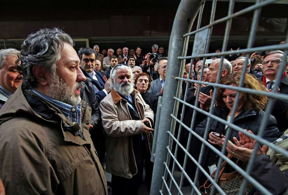 FILE - In this Jan. 18, 2015 file photo, Murat Sabuncu, chief editor of Cumhuriyet, talks to friends and readers outside his newspaper's headquarters in Istanbul. Turkish police detained the chief editor and at least eight senior staff of Turkey's opposition Cumhuriyet newspaper on Monday Oct. 31, 2016 in a continuing crackdown on dissenting voices. (Ugur Demir/Cumhuriyet via AP, File) Photo: Ugur Demir, SUB / Cumhuriyet