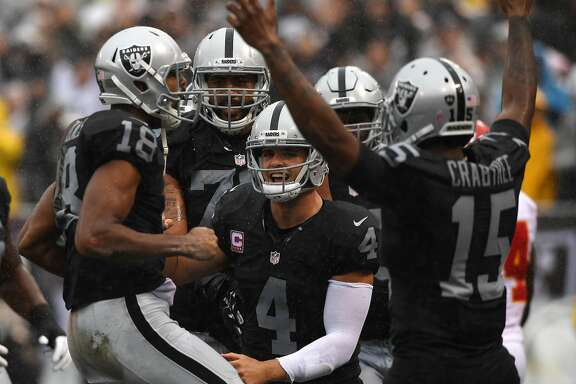 OAKLAND, CA - OCTOBER 16:  Derek Carr #4 of the Oakland Raiders celebrates after a three-yard touchdown with Andre Holmes #18 during their NFL game against the Kansas City Chiefs at Oakland-Alameda County Coliseum on October 16, 2016 in Oakland, California.  (Photo by Thearon W. Henderson/Getty Images)