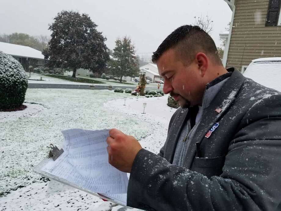Christopher Davis, a Republican running against incumbent Neil Breslin in the 44th Senate District, checks voter registration rolls as he campaigned door to door in Colonie on Oct. 27, 2016. (Chris Churchill/ Times Union)