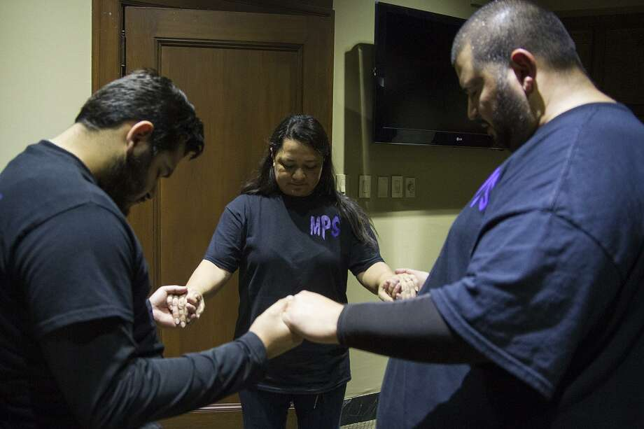 (Left to right) David Ramos, Suzie Martinez and Mike Cardenas, members of the Midnight Paranormal Society say a prayer before starting a paranormal investigation in the Express-News building, Sunday, Oct. 30, 2016. Photo: Alma E. Hernandez, For The San Antonio Express News / Alma E. Hernandez / For The San Antonio Express News