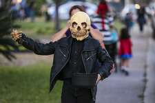 A boy wears his Ghost Rider costume as he trick-or-treats at the homes in Alexander Estates on Halloween night.