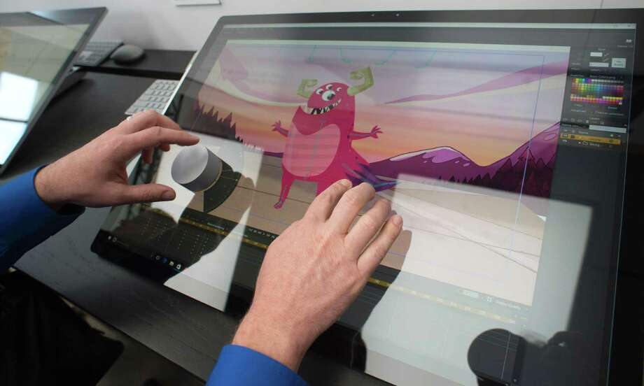 """Journalists and Microsoft fans get a look at the new Microsoft Surface Studio introduced at a Microsoft news conference October 26, 2016 in New York. Microsoft launched a new consumer offensive Wednesday, unveiling a high-end computer that challenges the Apple iMac along with an updated Windows operating system that showcases three-dimensional content and """"mixed reality.""""The US tech giant announced its first desktop computer, called Surface Studio, a $3,000 high-end """"all-in-one"""" device that aims at creative professionals, a segment dominated by Apple.  / AFP PHOTO / DON EMMERTDON EMMERT/AFP/Getty Images Photo: DON EMMERT, Staff / AFP or licensors"""