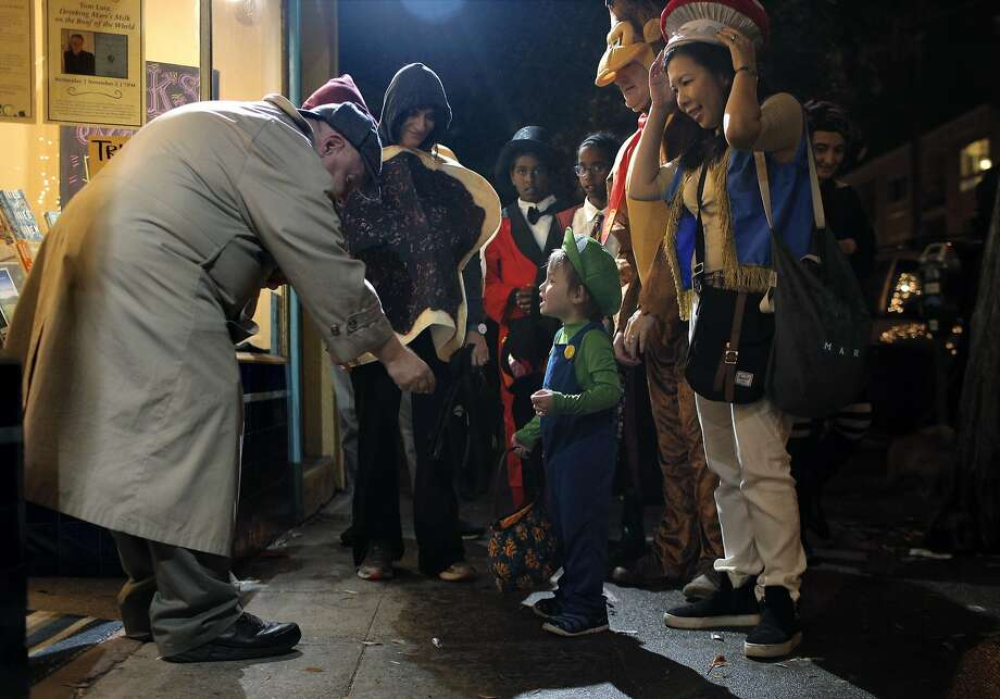 John Foley hands out candy to Jack Olsson, 3, as his mom Chiharu, and dad, Jim walk with him on 24th Street in Noe Valley as the city celebrated Halloween in San Francisco, Calif., on Monday, October 31, 2016. Photo: Carlos Avila Gonzalez, The Chronicle