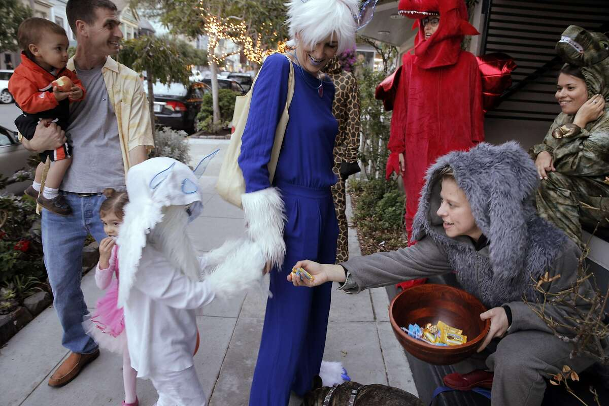 Miles Miesnieks, 7, gets a handful of candy with his mom, Silka, from Marie Van Wassenhoven, right, as they Trick-or-Treat on 24th Stree in Noe Valley as the city celebrated Halloween in San Francisco, Calif., on Monday, October 31, 2016.
